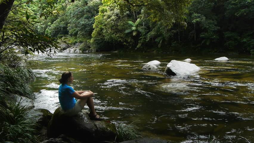 a tourist admires the tropical rain forest at mossman gorge in queensland, australia
