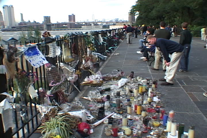 NEW YORK CITY - SEPTEMBER 29, 2001: Spectators look at memorials clustered on ground and hanging from fence on Brooklyn promenade.