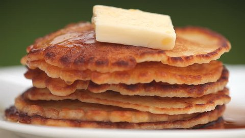 Closeup of stack of pancakes with pouring maple syrup