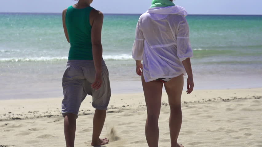 Two young girlfriends walking on the beach