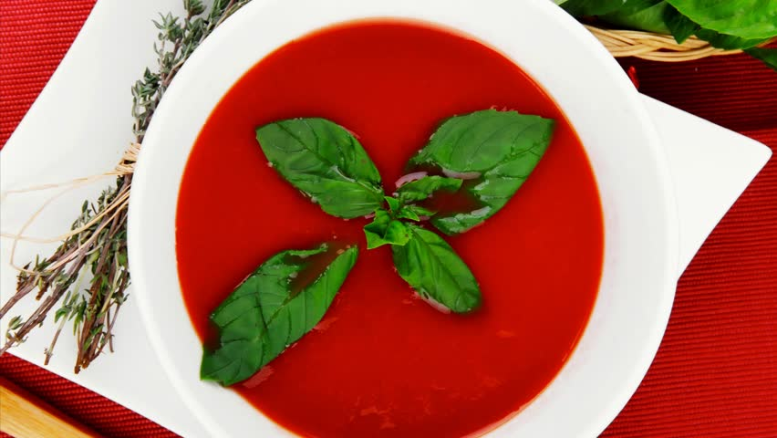 cold fresh diet tomato soup with basil thyme and dry pepper in big bowl over red mat on wood table ready to eat 1920x1080 intro motion slow hidef hd