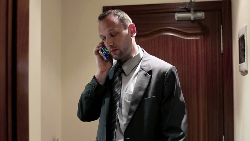 Young businessman talking on cellphone while getting into the hotel room