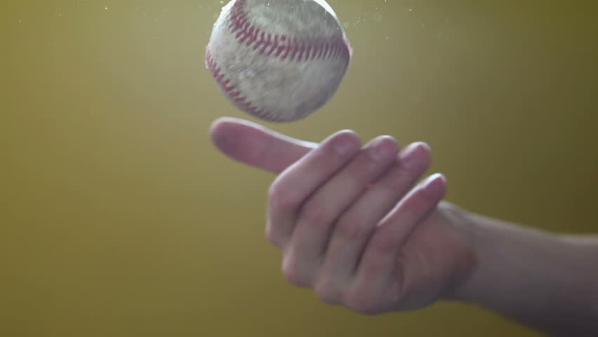 Tossing baseball in hand slow motion with lots of flare.