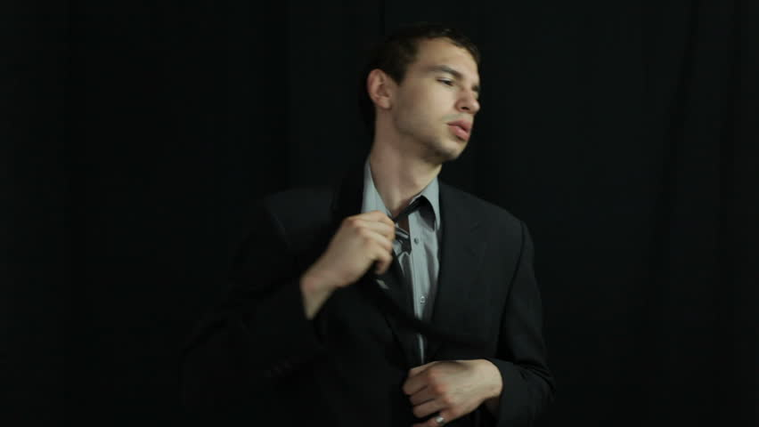 Uncomfortable businessman adjusting his necktie, over dark background