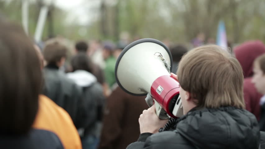 Portrait of a young man shouting with a megaphone at a crowded place