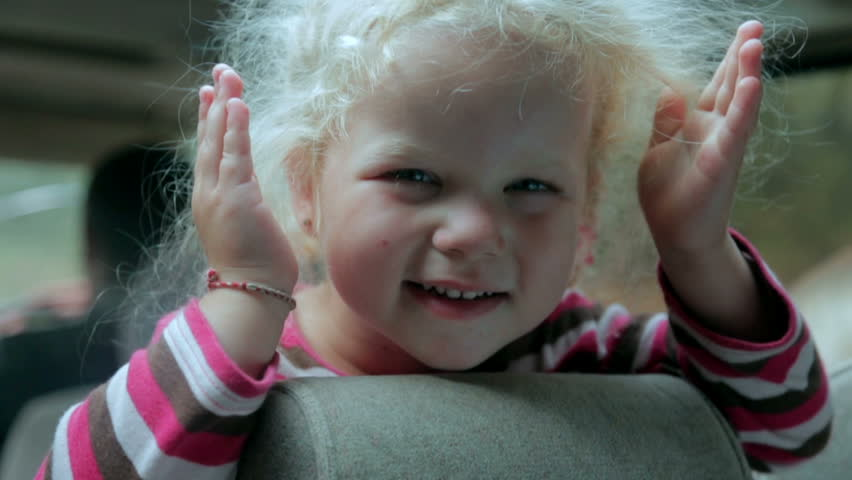 Happy little blond girl playing peek a boo in the car