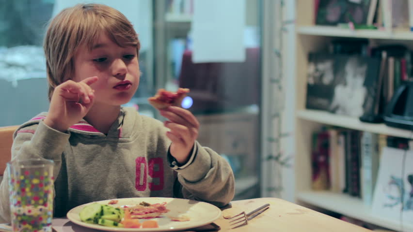 A young boy eats pizza at the dinner table, but he's easily distracted.