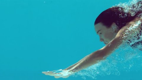 Brunette woman swimming underwater in slow motion