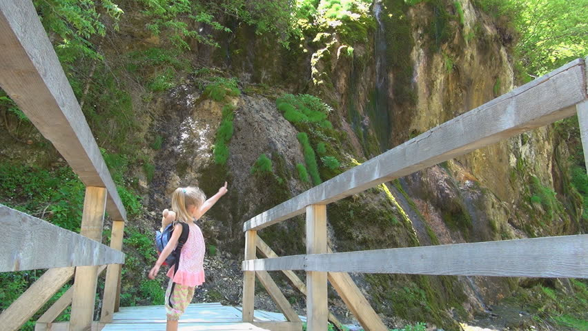 Child on a Bridge Pointing to a Spring in Mountains, Tourist in a Trip, Children