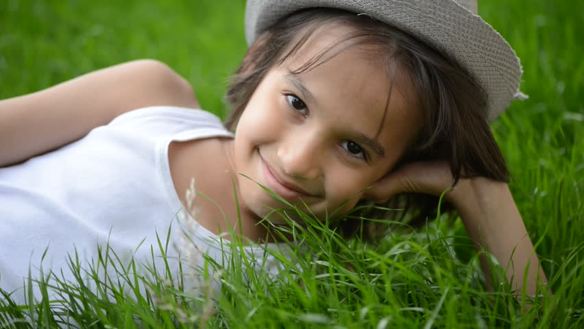 Happy child lying on green grass outdoors in spring park | Shutterstock HD Video #4006528