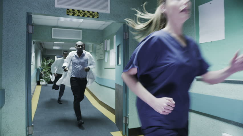 Doctor's and medical staff are running urgently through a hospital corridor to respond to an emergency situation. In slow motion.