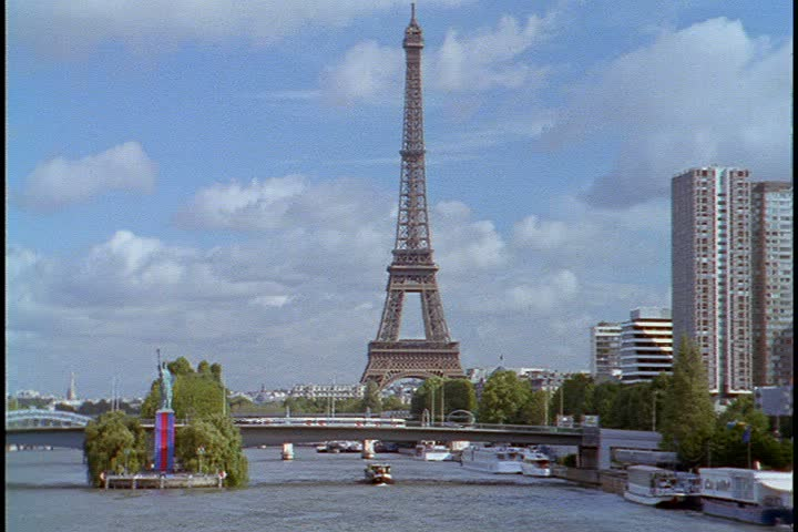 Tilt up from water to WS looking down the Seine River to the Eiffel Tower in Paris, France. A barge is traveling up the river. Copy of the Statue of Liberty on island in river.  | Shutterstock HD Video #4029148
