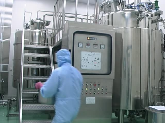 A technician pouring liquid medicine to a mixing machine in a pharmaceutical manufacturing factory.