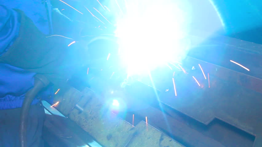Welding process as man in helmet lights up weld torch