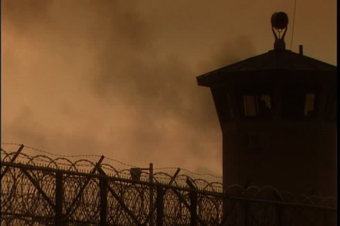 Silhouette of guard tower and barbed wire perimeter fence in morning mist  and haze at southern ohio correctional facility in lucasville, ohio