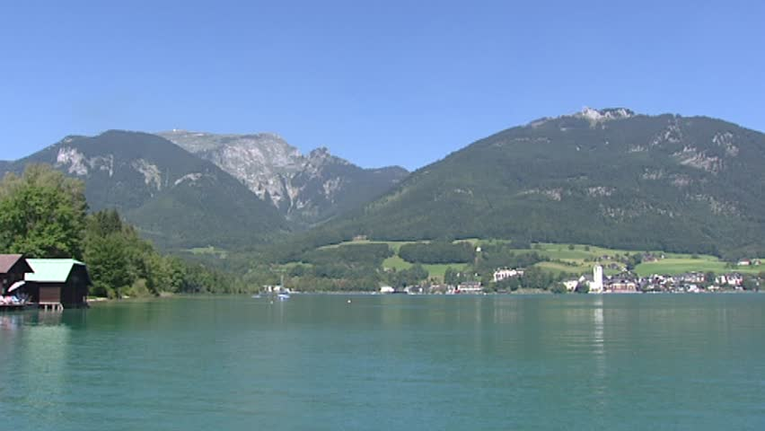 WOLFGANGSEE, SALZKAMMERGUT, AUSTRIA - AUGUST 2009: mountain lake pan lake shore with village at opposite side. Parts of the region were listed as a World Heritage Site in 1997. - HD stock footage clip