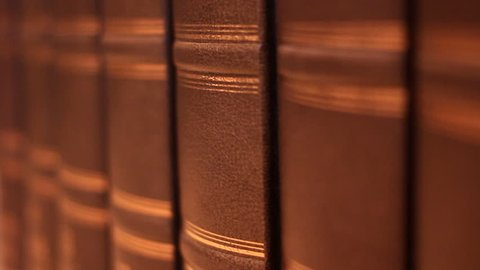 Books on the table in library, shallow depth of field. Book with a luxurious leather binding.