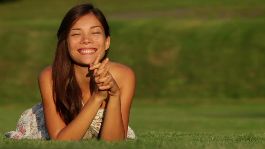 Young beautiful woman smiling lying in grass in summer dress outside at sunset waving hello looking at camera. Happy joyful mixed race girl of Asian Caucasian ethnicity.