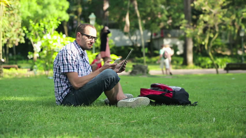 Young student using smartphone and tablet in the park