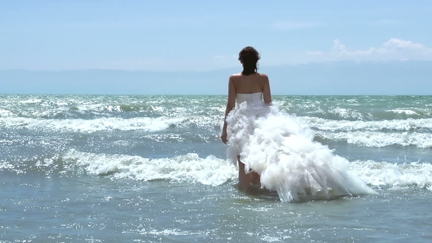 Mermaid wedding. The bride in a wedding dress with a lush trail walks in the waves. Slow Motion at a rate of 240 fps