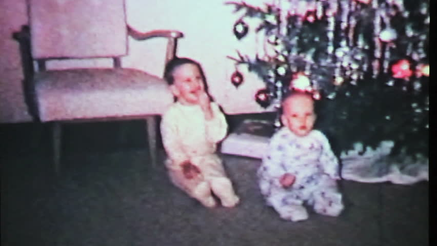 Cute little boys play around in front of the Christmas tree including getting scolded for touching the ornaments in 1965. #4159153