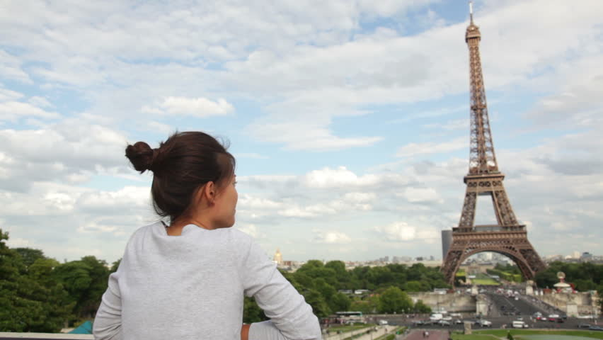 Paris Eiffel Tower woman tourist looking away and waving at camera during travel tourism sightseeing in Paris, France, Europe. Beautiful young mixed race Asian Caucasian traveler having fun.