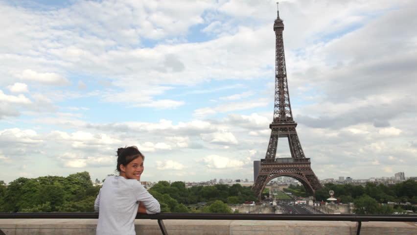 Eiffel Tower Paris woman tourist enjoying view and waving looking away and waving at camera during travel tourism sightseeing in Paris, France, Europe. Beautiful young Asian Caucasian traveler