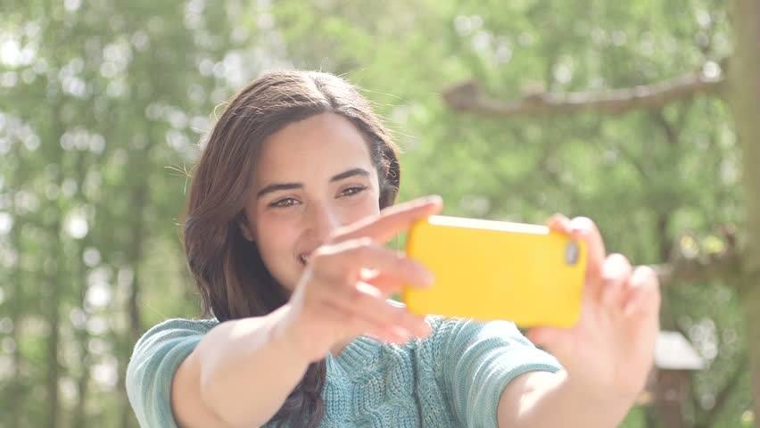 Young woman taking self portrait with smartphone