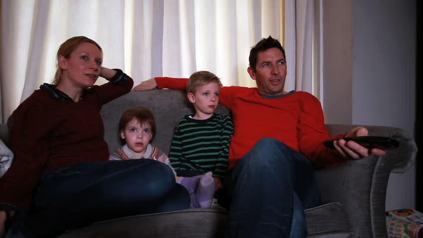 Family relaxing on sofa together watching tv