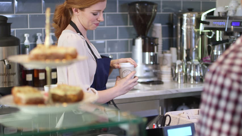 Female seller serving young man coffee to go - HD stock footage clip