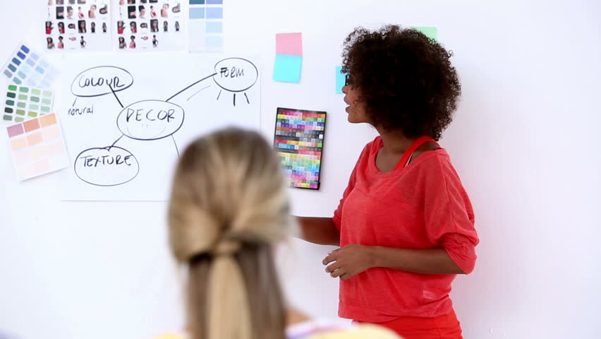 Pretty designer pointing at a plan on a wall during a meeting
