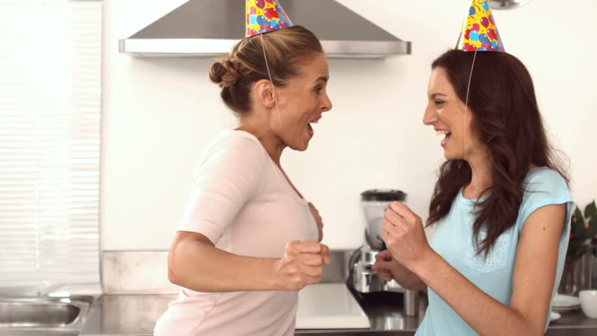 Two pretty friends dancing together in the kitchen while wearing party hats in slow motion