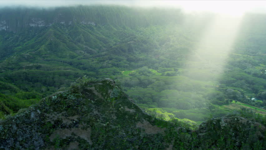 Aerial view of sun rays on volcanic cliffs covered in rich fertile tropical landscape, Hawaii, Oahu, USA, RED EPIC | Shutterstock HD Video #4244198