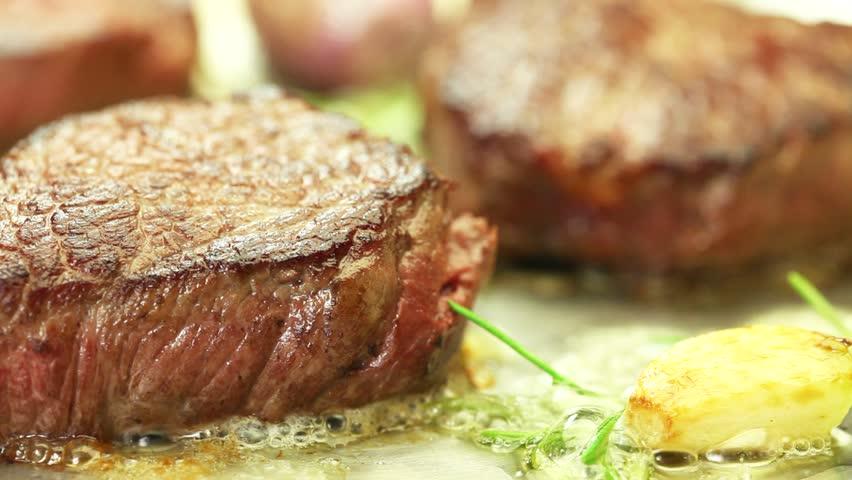 Beef fillet steak being fried in butter