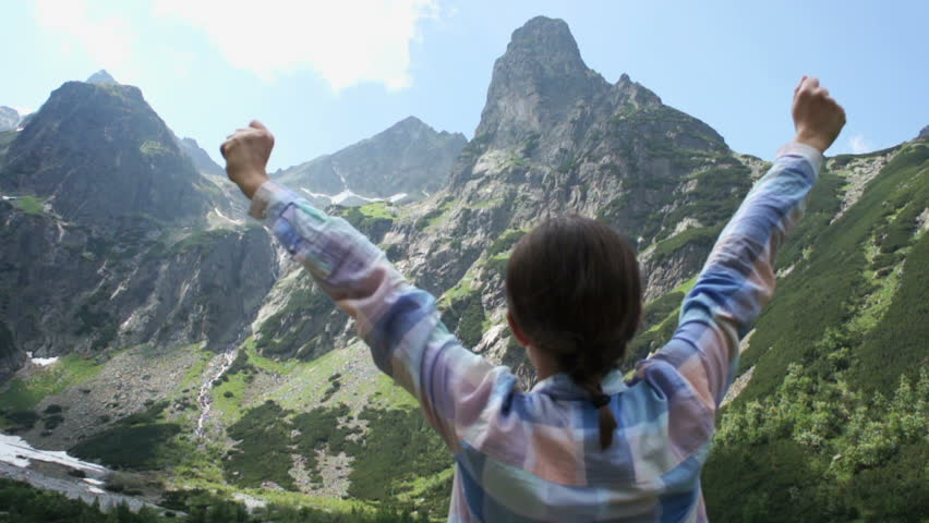 Successful woman raising hands on the top of mountain