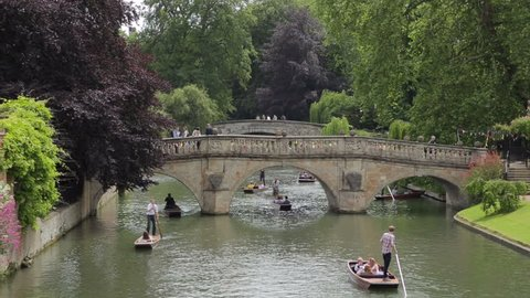 CAMBRIDGE, CAMBRIDGESHIRE/ENGLAND - JUN 27: Unidentified people punt on River Cam, Clare Bridge in background on Jun 27, 2013 in Cambridge. Punting has been a Cambridge tradition for over 100 years.