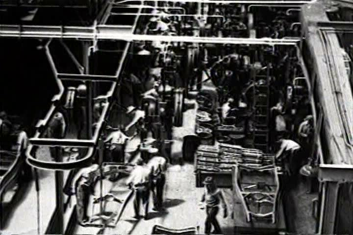 1930s - Great long traveling aerial shot over a factory with workers in 1932.