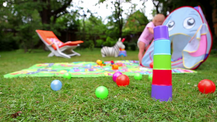 Toys on grass and unrecognizable baby on background (dolly shot)