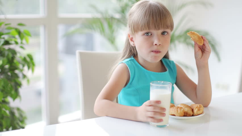 Funny little girl sitting at table drinking milk and eating cakes and smiling at camera
