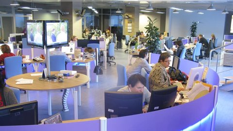 MOSCOW - MAR 05: (timelapse) People working at the office with big screen behind at RIA Novosti, on Mar 05, 2013 in Moscow, Russia.
