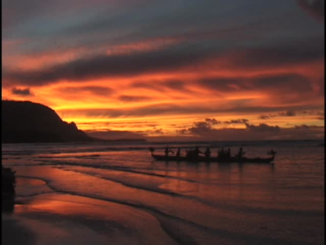 Fire red sunset silhouette of Hawaiian outrigger boat with crew and distant  mountain range.