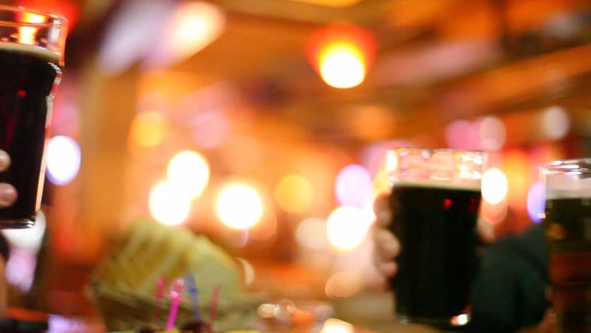 Four hands clink glasses goblet with beer