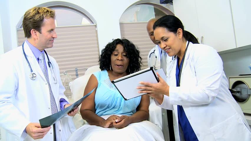 Multi ethnic male radiologists Hispanic nurse showing senior ethnic female latest x-ray results | Shutterstock HD Video #4330973