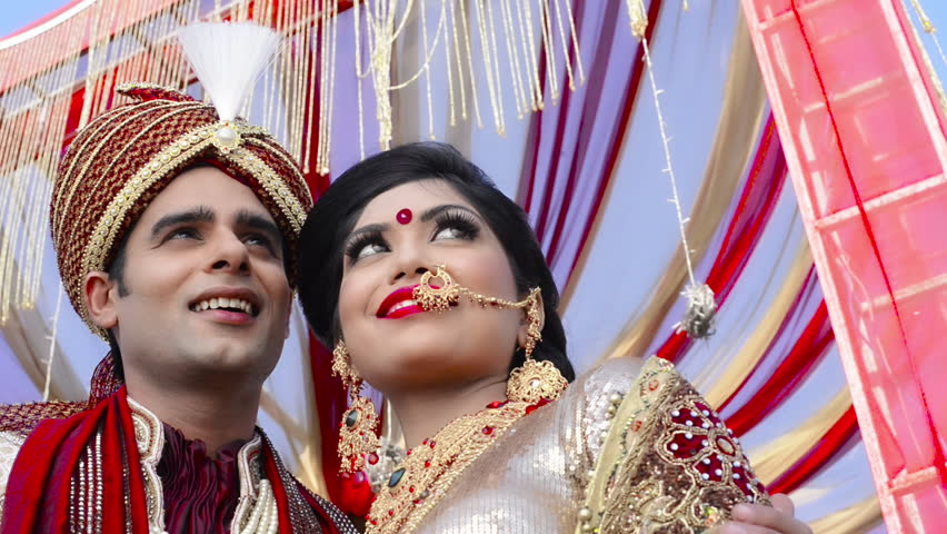 2c484a2e13 Pan shot of Indian bride and groom in traditional wedding dress posing  under a mandap
