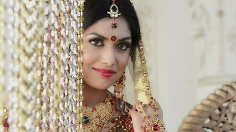 Pan shot of a happy Indian bride posing