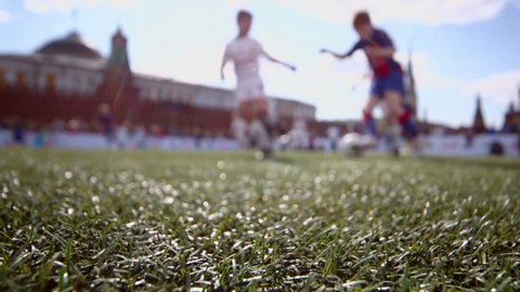 Boy play football on Red Square near Kremlin at sunny day in Moscow, (focus on grass)