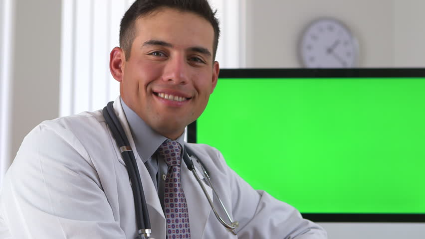 Hispanic doctor smiling with green screen on computer in background