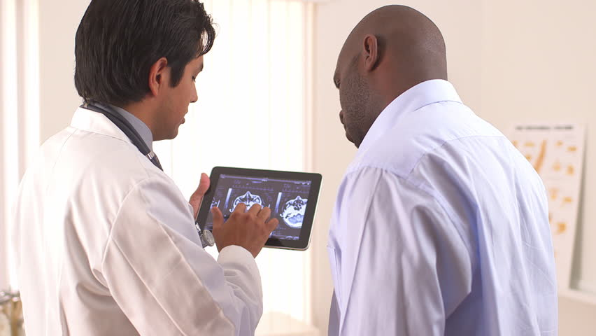 Hispanic doctor using tablet pc to share MRI with patient | Shutterstock HD Video #4378238