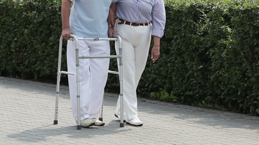 Male retiree doing step after step with a walker, his wife supporting him