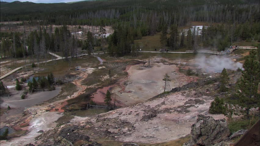 Aerial view of Yellowstone National Park with tourists and smoking geyser